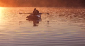 Romantic golden sunset river lake fog loving couple small rowing boat Romantic date beautiful Lovers ride boat during beautiful su Stock Image