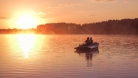 Romantic golden sunset river lake fog loving couple small rowing boat Romantic date beautiful Lovers ride boat during beautiful su Royalty Free Stock Photos