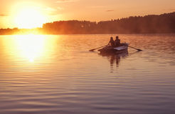 Romantic golden sunset river lake fog loving couple small rowing boat Romantic date beautiful Lovers ride boat during beautiful su Stock Photo