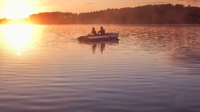 Romantic golden sunset river lake fog loving couple small rowing boat Romantic date beautiful Lovers ride boat during beautiful su Stock Photos