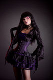 Romantic gothic girl in purple and black gothic Halloween outfit. Studio shot on black background Royalty Free Stock Images