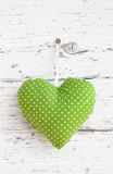 Romantic green dotted heart shape hanging above white wooden surface on a nail- white wooden shabby chic background for royalty free stock photography