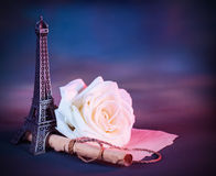Romantic greeting card. Image of festive greeting card with fresh white rose on the table decorated with small Eiffel tower, vintage photo, wedding in Paris Royalty Free Stock Images
