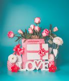 Romantic greeting setting with word LOVE, gift box, heart, bunch of pink pale roses , white bottle of champagne and glasses. On turquoise blue background, front Stock Image