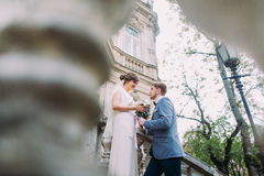 Romantic groom giving bouquet to his beautiful bride on the stairs of antique austrian house Stock Photography