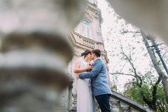 Romantic groom giving bouquet to his charming bride on the stairs of antique austrian building stock images