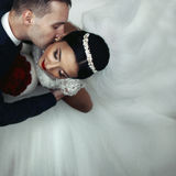 Romantic groom kissing brunette bride on the neck, shot from abo Stock Photography