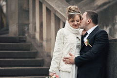 Romantic groom kissing happy bride in coat on stone stairs Stock Images