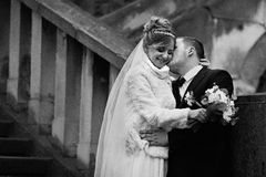 Romantic groom kissing happy bride in coat on stone stairs b&w Stock Photos