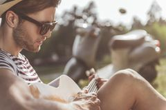 Romantic guy composing melody with calmness. Profile of pensive young man sitting in forest and playing guitar. He is wearing sunglasses and hat. Scooter on Royalty Free Stock Image