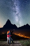Romantic guy embracing red-haired girl and shows on stars and Milky way in beautiful starry sky at night Royalty Free Stock Photo
