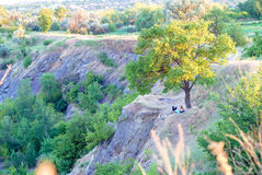 A romantic guy and a girl on the slope of a granite quarry shot from afar in the sunset. Stock Image