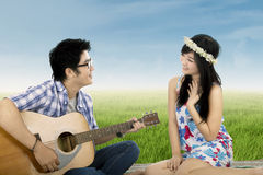 Romantic guy playing guitar for his girlfriend Stock Images