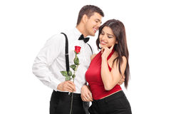 Romantic guy whispering something to a girl. And holding a red rose isolated on white background Royalty Free Stock Photos