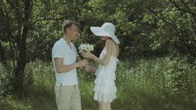 Romantic man giving flowers to his cute girlfriend. Romantic handsome man giving bunch of fresh chamomiles to his beautiful elegant girlfriend during romantic stock video footage