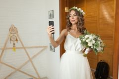 Romantic and happy caucasian bride in stylish wedding dress taking selfie on the background of beautiful room. Taking the bouquet in hand stock image