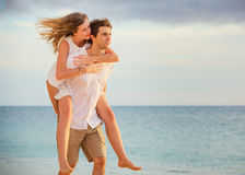 Romantic happy couple on the beach at sunset Royalty Free Stock Photos