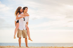Romantic happy couple on the beach at sunset Royalty Free Stock Images