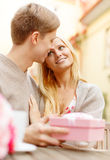 Romantic happy couple with gift in the cafe Royalty Free Stock Photography