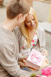 Romantic happy couple with gift in the cafe stock images