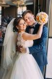 Romantic happy couple, groom embracing his bride near window closeup.  Stock Photography