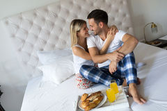 Romantic happy couple having breakfast in bed Royalty Free Stock Images