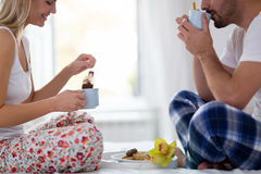 Romantic happy couple having breakfast in bed. Romantic young happy couple having breakfast in bed Royalty Free Stock Images