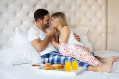 Romantic happy couple having enjoying each other on bed. And having breakfast Stock Photos