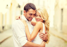 Romantic happy couple hugging in the street. Summer holidays, love, travel, tourism, relationship and dating concept - romantic happy couple hugging in the Royalty Free Stock Image