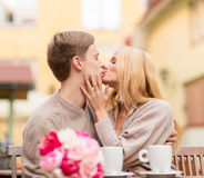 Romantic happy couple kissing in the cafe. Summer holidays, love, travel, tourism, relationship and dating concept - romantic happy couple kissing in the cafe Stock Photo
