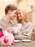 Romantic happy couple kissing in the cafe. Summer holidays, love, travel, tourism, relationship and dating concept - romantic happy couple kissing in the cafe Royalty Free Stock Photos