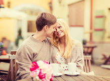 Romantic happy couple kissing in the cafe. Summer holidays, love, travel, tourism, relationship and dating concept - romantic happy couple kissing in the cafe Royalty Free Stock Photography