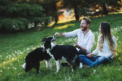 Romantic happy couple in love enjoying their time with pets. In nature Royalty Free Stock Photo