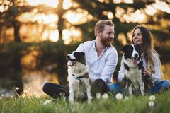 Romantic happy couple in love enjoying their time with pets. In nature Royalty Free Stock Photography