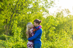 Romantic happy couple in love on nature. Man and woman kissing in summer park. Romantic happy couple in love on nature. Man and women kissing in summer park Royalty Free Stock Photos