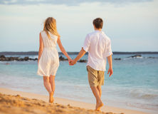 Romantic happy couple walking on beach at sunset Stock Image