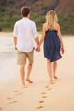 Romantic happy couple walking on beach at sunset Royalty Free Stock Image