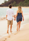 Romantic happy couple walking on beach at sunset Stock Photography