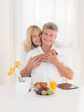 Romantic happy mature couple with beautiful smiles hugging on breakfast. This happy smiling mature senior couple sits at a healty breakfasst, while the wife Stock Photography