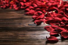Beautiful bright red rose petals on wooden background. Happy valentines day oliday sales concept. Romantic happy valentines day greeting card / women`s day Stock Photos