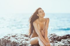 Portrait of beautiful young woman on wild rocky beach. Romantic happy young girl in bikini outdoors against wild tropical sea background. Portrait of beautiful Royalty Free Stock Photos