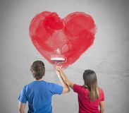 Romantic heart couple. Young couple drawing a big heart in a wall Stock Photography