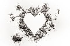 Romantic heart love symbol made in ash, dust or sand. As burning bursting passion, painful emotion for valentines day concept, burnt feelings background stock photo