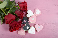 Romantic heart shape pink, white and black cookies with red roses Stock Image