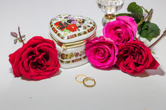 Romantic heart shaped artistic jewelry box with bright red and pink roses with gold engagement rings on light background. stock image