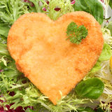 Romantic heart shaped fried golden schnitzel. In breadcrumbs served on a bed of fresh leafy green lettuce and basil and garnished with parsley royalty free stock images