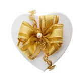 Romantic heart shaped gift and gold bow. Fastened with a pearl and braid for a loved one or sweetheart on Christmas, Valentines, birthday or an anniversary Royalty Free Stock Photography