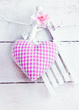 Romantic Heart On snowy Boards. Romantic checked snowy needlework heart for Valentines hanging on snow white boards with copyspace Stock Image