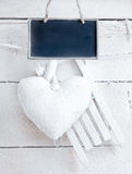 Romantic Heart On White Boards. Romantic checked snowy heart for Valentines hanging on snow white boards with tag Stock Photography