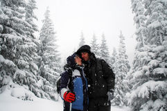 Romantic hiking couple embracing in the winter mountains stock photography